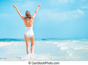 Young woman in swimsuit walking on sea coast rear view