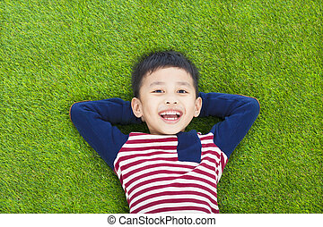 smiling kid lying and holding his head