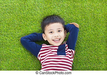 happy kid lying and holding his head on a meadow