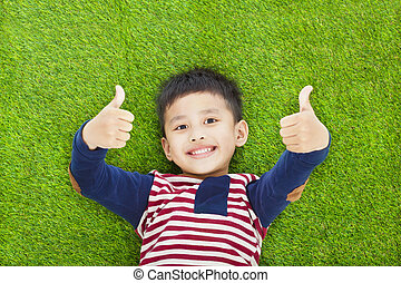 happy kid lying and thumb up  on a meadow