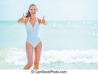 Happy young woman in swimsuit on sea shore showing thumbs up
