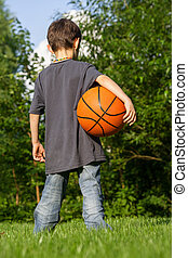 Little basketball player in the garden
