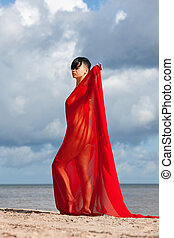 naked woman on a beach with red fabric - Young naked woman...