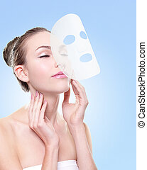 Relax Young woman with cloth facial mask isolated on blue...