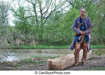 At The River - Indian warrior by his homemade canoe.