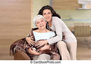 elderly woman and her daughter sitting in a chair with a blanket, hug, mother, grandmother