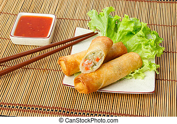 Fried spring rolls, one cut, on a plate served with chili...