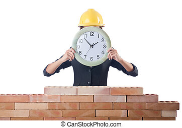 Woman construction worker with clock on white