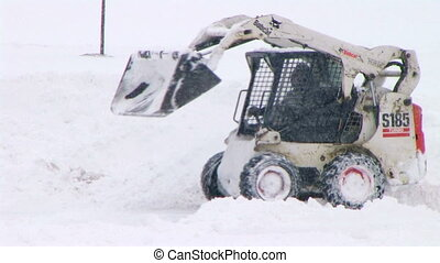 Bobcat Plowing Snow - Bobcat plowing snow in parking lot.