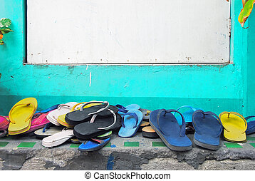 Slippers of visitors in front of white door