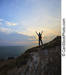 young man standing on rock clift and rising victory hand against dusky sky background