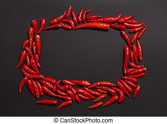 Frame made of non-stem red bird eye chili peppers on grey...