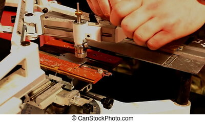 Metal engraving work - Engraver is cutting letters on the...