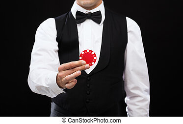 dealer holding red poker chip - magic, performance, circus,...