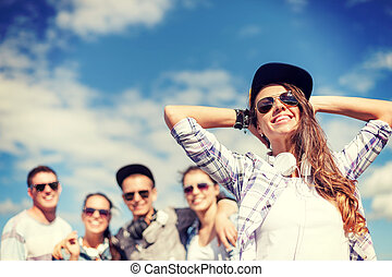 teenage girl with headphones and friends outside - summer...