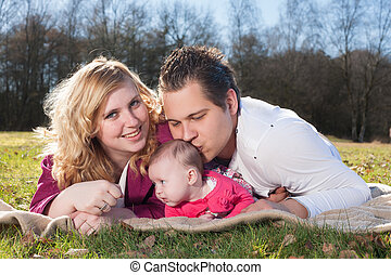 Daddy is kissing his girl - Young family is having nice time...