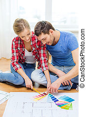 smiling couple looking at color samples at home - repair,...