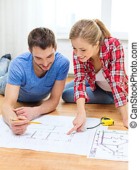 smiling couple looking at blueprint at home - repair,...