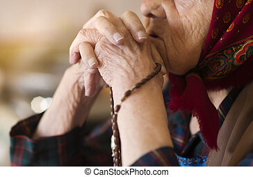 Old woman praying - Detail of very old woman in head scarf...
