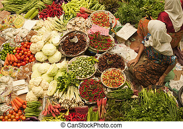 Vegetable market. - Muslim woman selling fresh vegetables at...