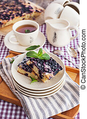 Portion of fresh homemade blueberry cake and cup of tea on...