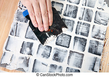 grout - worker applies grout at grey tiles