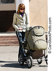 Mother with baby carriage - happy mother with baby carriage...