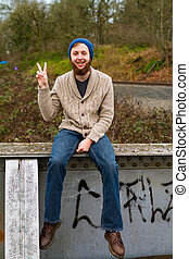 Hippie Peace Sign - Hippie man sitting on a bridge giving a...