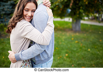 In embrace - Happy girl embracing her boyfriend in park