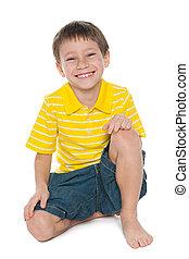 Little happy boy - A little happy boy is sitting on the...