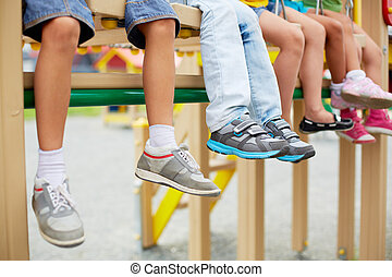 Legs of kids - Legs of little friends sitting on swing or...