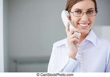 Speaking by the phone - Young businesswoman looking at...