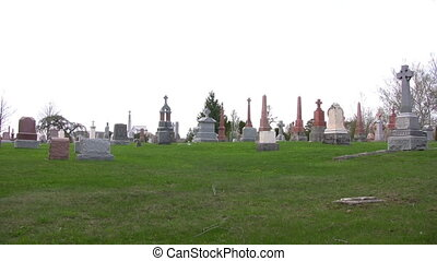 Cloudy day at the cemetery - A slight pan of a cemetery and...