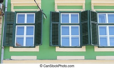 Green Windows with Shutters - Pan shot with shapely row of...