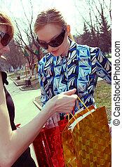 shopping women - women shows her shopping bags in a city...