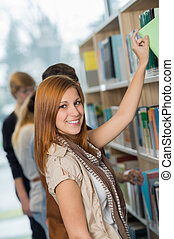 Student taking book from bookshelf in library - Student...
