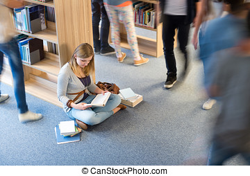 Student sitting floor in library blur motion - Student...