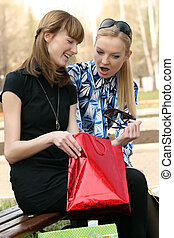 best friends after shopping - woman shows a sunglasses her...