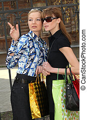 shopping women - Shopping women with bags pointing out...