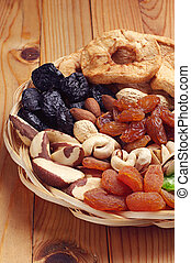 Dried fruits and nuts on a natural wooden background