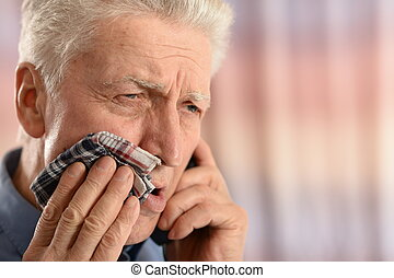Sick old man with tooth pain standing on colored background