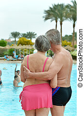 Senior couple standing by pool at the resort during vacation