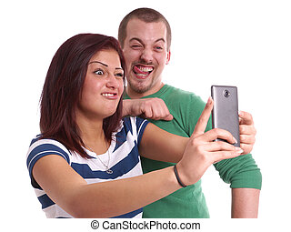young couple taking selfie - making silly faces while taking...