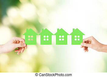 man and woman hands with many green paper houses - real...