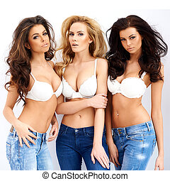 Three gorgeous sexy young women posing arm in arm in jeans...