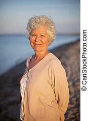 Beautiful old woman standing alone at the beach - Portrait...