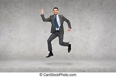 smiling businessman jumping - business and education concept...