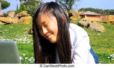 Asian woman with pc in park