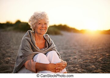 Smiling old woman sitting on the beach - Portrait of smiling...
