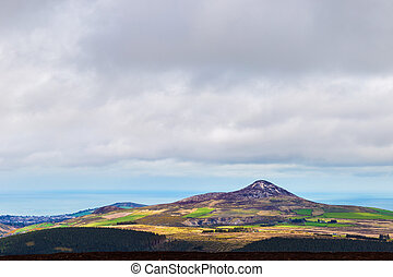 Sunlight hitting Sugar Loaf on a cloudy day